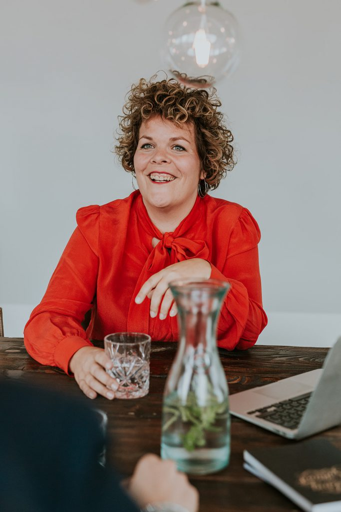 Lachend aan tafel om online jouw naamsbekendheid te vergroten